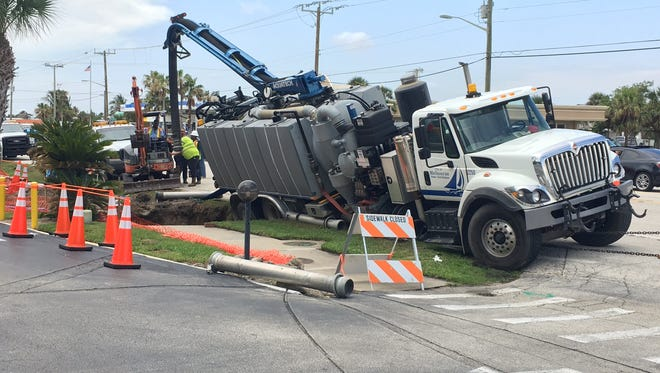 A city truck stuck in a hole blocked State Road A1A in Satellite Beach.