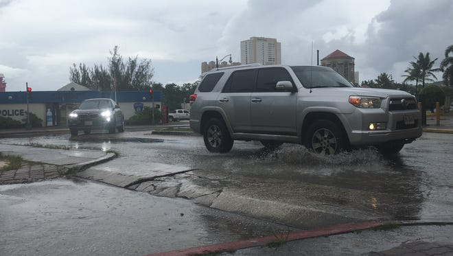 Cars splash through standing water as they turn left  from Pale San Vitores Road onto Happy Landing Road in Tumon on June 19. The Guam Economic Development Authority this week announced the second phase of the Tumon flood mitigation has started and will continue through November. More storm drains will be installed at both ends of Happy Landing Road and on Fujita Road.