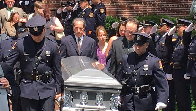The casket for Linden Officer Daniel Kuczynski is carried from the church.
