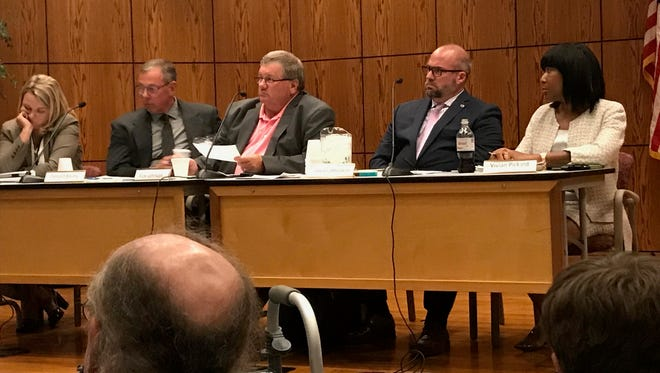 Chairman Rick Johnson (center) and other members of the Medical Marijuana Licensing Board hear from the public Monday at the board's first meeting in Lansing.