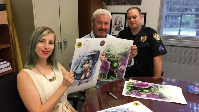 From left, artist Bella Rachlin displays her depiction of Wonder Woman; Morristown Mayor Timothy Dougherty, and town Police Sgt. Michael Molnar.