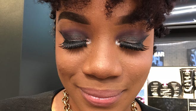 NYX Professional Makeup sales associate Jourdan Bowers shows off her sparkly eye shadow.