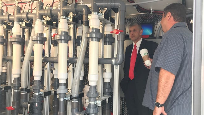 Indian River County Commissioner Joseph E. Flescher inspects reactor tubes that are part of a system designed to keep pollution out of the Indian River Lagoon during a demonstration Tuesday in Vero Beach by Michigan-based Greenfield Resources.