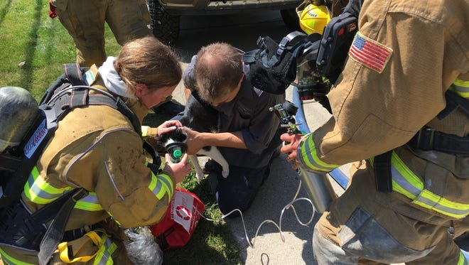Firefighter Dana Timm holds a rescued a cat from a house fire Monday morning from a home on Grantland, while firefighter Chris Audette holds the bottle full of oxygen. Crews used an oxygen mask designed for pets during the rescue. Fire officials say the cat appeared to be fine.