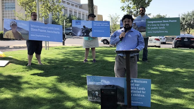 Lucas Herndon, with the ProgressNow NM Education Fund, speaks at a rally Thursday at Albert Johnson Park in Las Cruces. Behind him, members of the group Step Up Steve hold advertising signs created to challenge U.S. Rep. Steve Pearce, R-N.M.