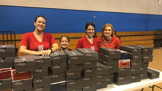 Junior League of San Angelo members Catherine Gossett, Cortney Wilkerson and Stacy Greaves prepare to distribute new shoes at the Southside Rec Center on Thursday, Aug. 3.