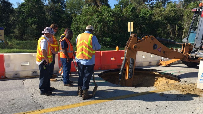 Crews work to repair a hole where a sewer line broke on Knox McRae Drive in Titusville. The whole was easily mistaken for a sinkhole.