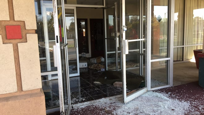 The front doors of the former Red Carpet Inn have been broken out and stand open.
