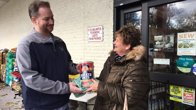 Morristown Police Sgt. Michael Molnar accepts a donation from Kings shopper Cheryl Eggert during PBA 43's 'Fill A Cruiser' campaign on Nov. 19, 2017.