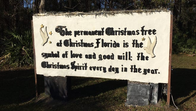 A sign shares the message behind the permanent Christmas tree in Christmas, Florida.