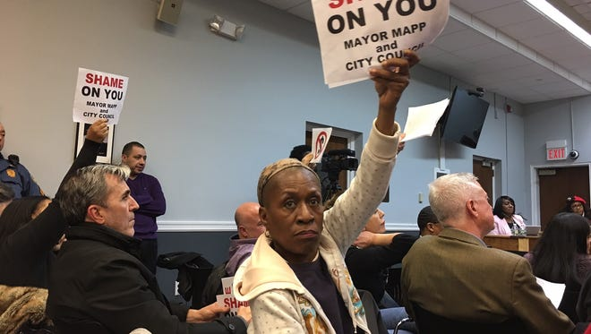 Plainfield residents raise signs during council meeting in which raises were approved for mayor and council members