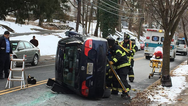 Morristown firefighters start the process of extricating a driver from her Honda Civic that overturned on Western Avenue in Morristown on Dec. 17, 2017.