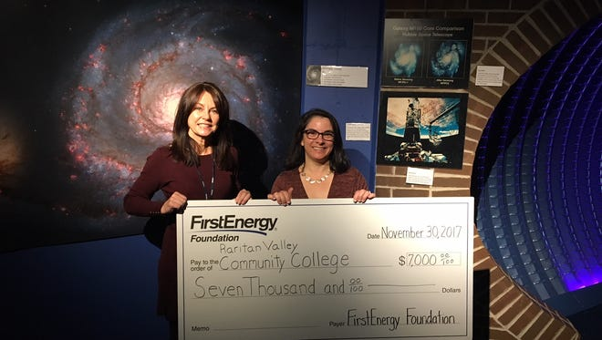 Jackie Espinoza (left), JCP&L Area Manager, presents a check from the FirstEnergy Foundation to Raritan Valley Community College Planetarium Director Amie Gallagher.