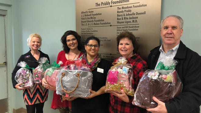 Danny Steed, far right, broker of Hirschi Realtors, and his wife, Maureen, presented some 40 purses and 30 cosmetic filled with goodies to Faith Refuge, the women's shelter. Maureen recruited members of the Hirschi Team to assist in collecting purses, hoping to get five to 10, and the group surpassed that goal.