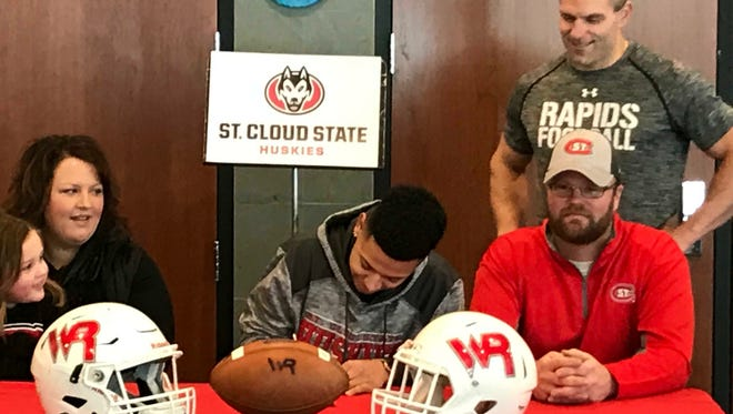 Wisconsin Rapids standout wide receiver Isaiah Westfall is joined by mom Carissa (left) and dad David as he signs his letter of intent with St. Cloud State during a ceremony Wednesday. Raiders football coach Tony Biolo looks on.