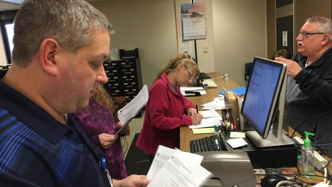 Delaware County Clerk Mike King (left) helps candidates file for office shortly before Friday's noon deadline.