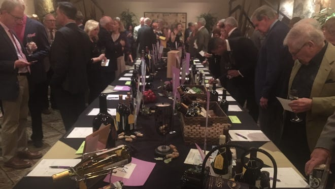 Attendees of the Coachella Valley Volunteers in Medicine Wine Lover's Auction examine the silent auction on Saturday, Feb. 17, 2018, at Thunderbird Country Club.