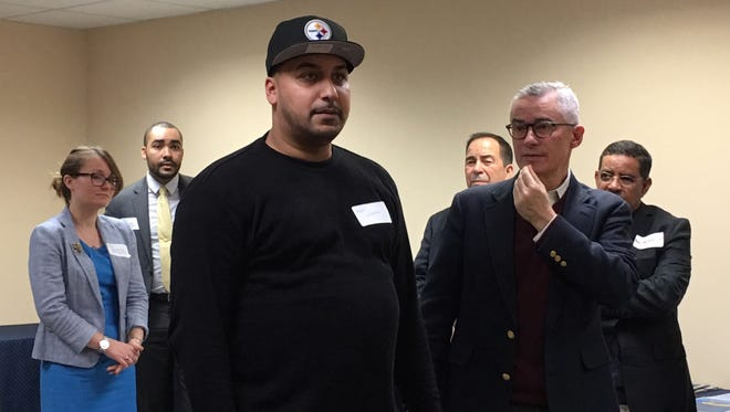 Angel Villafane standing next to former New Jersey Gov. Jim McGreevey speaks about the New Jersey Reentry Corporation program.