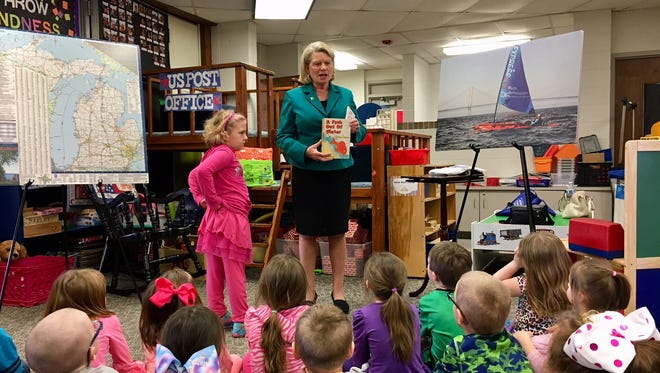 """Michigan Secretary of State Ruth Johnson shows Highland Elementary kindergarten students her copy of """"A Fish out of Water,"""" which she described as """"an antique"""" she's had since her own kindergarten year."""
