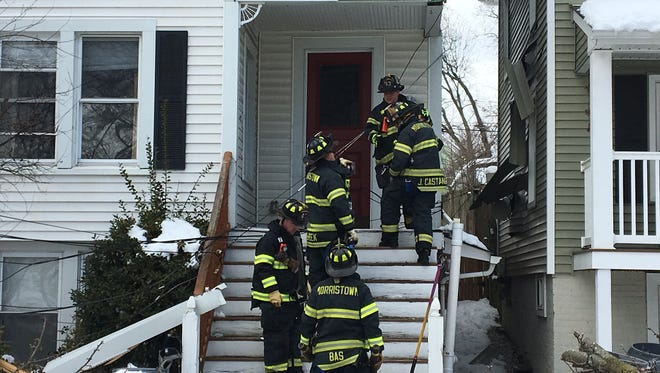 Morristown firefighters start to brace a house that was damaged when a truck on James Street pulled down a phone line, and part of the house to which it was attached on March 9, 2018.