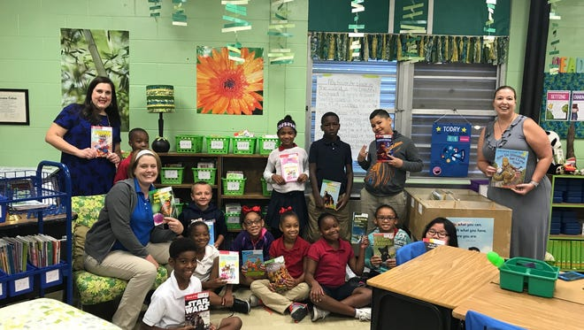 Laura Downing and her third grade class at Carencro Heights Elementary are pictured here last year with their new mobile library funded by a Cox Charities grant.