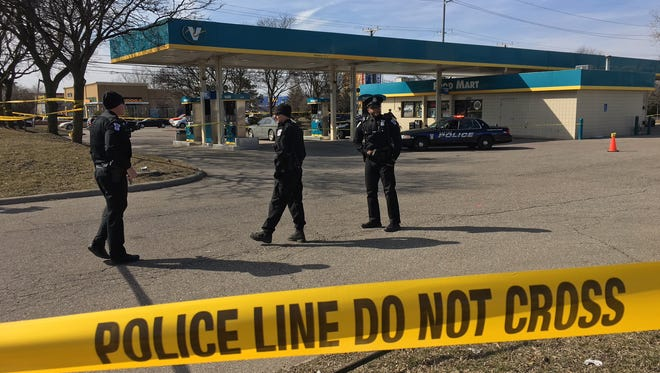 Police officers on Tuesday at the Valero gas station in Canton Township where a man was shot and an acquaintance taken into custody.