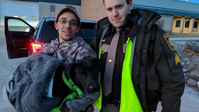 Buddy Boy, his owner, and Sgt. Zitlow of the Fond du Lac County Sheriff's Office stand safely on shore after Buddy Boy was rescued from the ice.