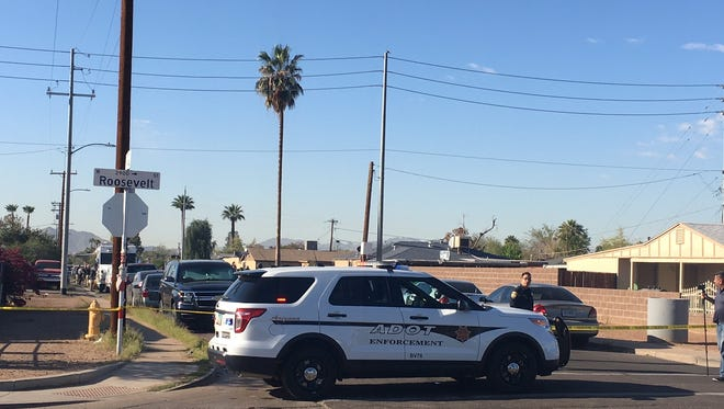 Police tape surrounds the area where officers shot and killed a man who pointed a gun at them as they were trying to serve a search warrant in a fraud/identity theft investigation by the Arizona Department of Transportation on March 27, 2018, in Phoenix.