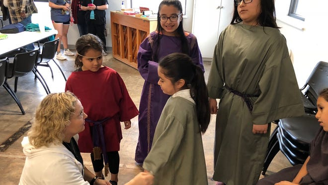 """Brooks Cain, coordinator of Thursday @ the Heights at Floral Heights United Methodist Church, directs the students in the Easter pageant """"The Empty Tomb."""""""