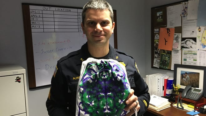 """Randolph Police Sgt. Matt Rispoli holds a """"Brave Bag,"""" a backpack filled with toys donated by residents of the Matheny School to calm children in distress."""