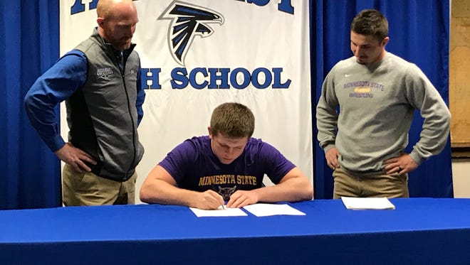 Amherst state runner-up wrestler Max Villnow is joined by Falcons coach Charlie Wanty (right) and former Falcons coach Dave Peterson as he signs a letter of intent to wrestle at Division II Minnesota State University-Mankato on Friday.