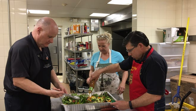 From left, Morris County Sheriff James Gannon, Amy Bucco and state Assemblyman Anthony M. Bucco, R-Boonton, mix the salad as part of their dinner preparation April 3 at Morristown's Table of Hope community soup kitchen.