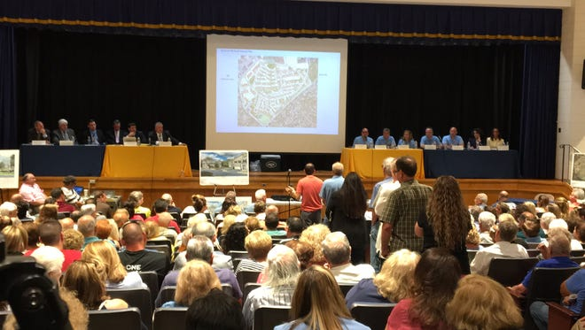 More than 1,000 East Hanover residents packed the East Hanover Middle School June 25 to hear township officials explain a plan by KRE Acquisitions to build 607 townhouses and apartments on River Road.