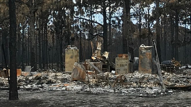 The burned husks of kitchen appliances and a water heater are all that remain of this house after the Limerock Wildfire June 24 destroyed 36 homes.