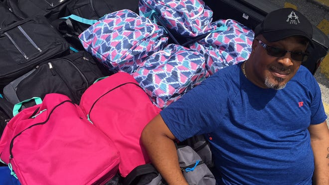 Rockledge resident Juan Mallory is pictured with a few of the 101 filled backpacks he delivered to Golfview Elementary School on July 30.
