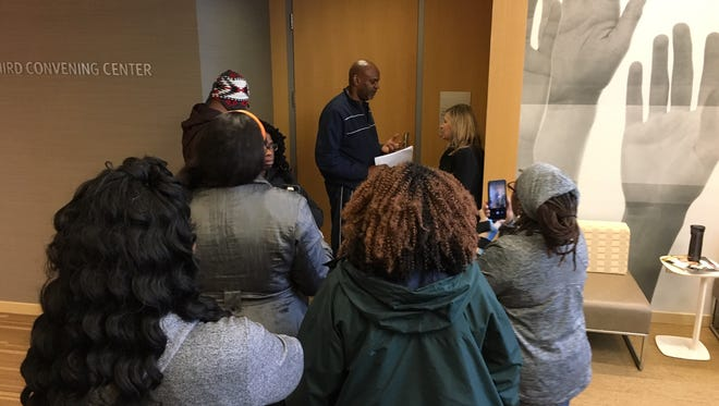 Led by the Rev. Damon Lynch III, some leaders of the city's black community Friday morning prepare to interrupt the private board meeting at the United Way of Greater Cincinnati. United Way communications executive Teresa Hoelle speaks with Lynch at the door.