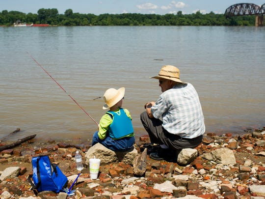 Joseph Hicks, 5, sits along the Ohio River fishing with his grandfather, Leon Hicks, both of Henderson, during the Come on Down to the River event at Audubon Mill Park, in Henderson, Saturday, July 16, 2016.