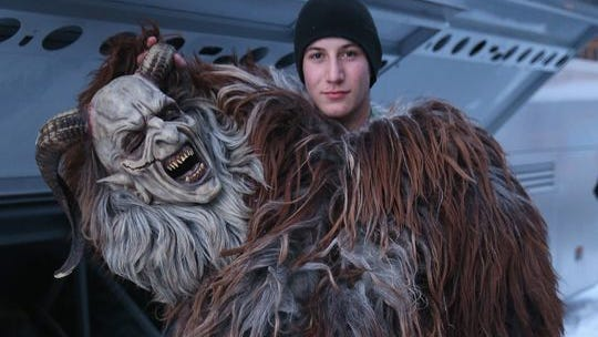 A man holds up his Krampus mask while dressing as the Krampus creature prior to Krampus night on Nov. 30 in Austria.