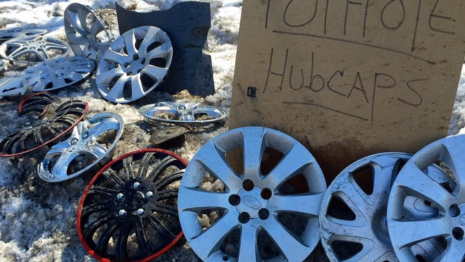 Hubcaps from cars that hit a pothole in Randolph collect on the side of the road.