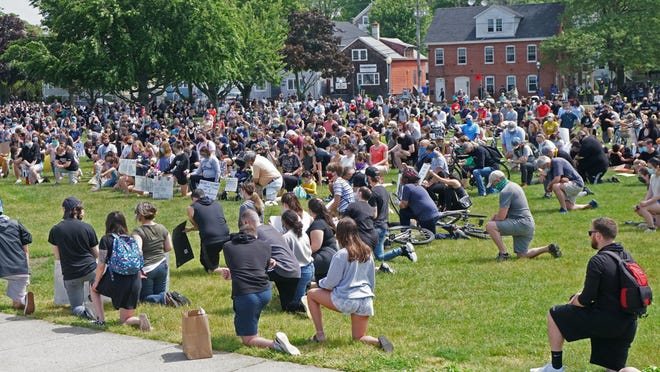 At Independence Park in downtown Bristol, hundreds of protesters get down on one knee Saturday to observe eight minutes and 46 seconds of silence in memory of George Floyd, the black man killed by the police in Minneapolis.