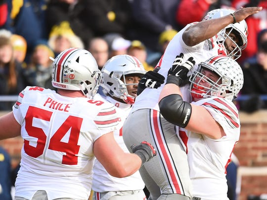 Ohio State quarterback J.T. Barrett celebrates with his teammates after scoring a touchdown in last year's 42-13 win over Michigan.