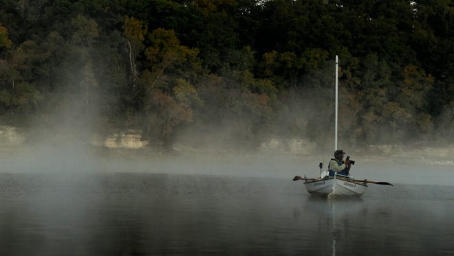 John Guider takes pictures as fog rises and the sun comes up to start the day along the Tennessee River on Oct. 12, 2016, in Parsons, Tenn.