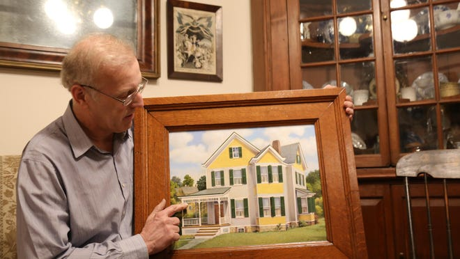 Robert Williams points to a painting he commissioned by local artist Mike Jaroszko of the Hadaway House on Union Street in the village. The frame is made from the woodwork at Beaver Dam Stock Farm.