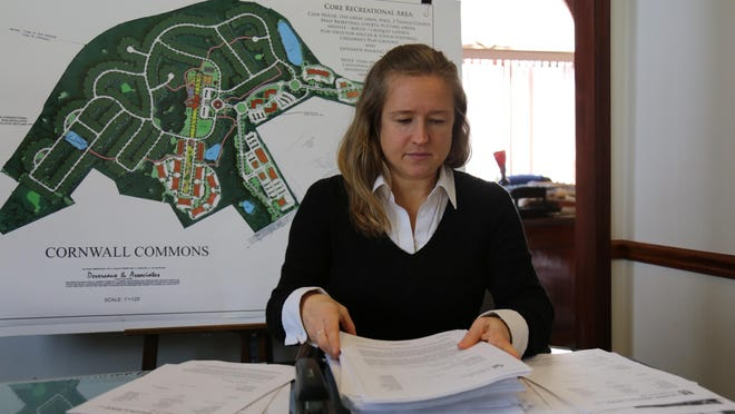 Developer Christina Amato organizes piles of documents regarding Cornwall Commons, a project that would build 490 homes for active seniors 55 and older on 197 acres west of the interchange of routes 9W and 218 in the Town of Cornwall.