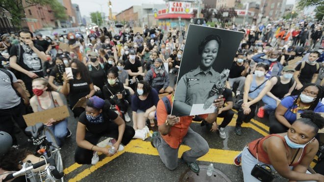 A man holds a photograph of Breonna Taylor on her birthday as he kneels with other protesters on Atlantic Avenue during a solidarity rally for George Floyd on Atlantic Avenue, Friday, June 5, 2020, in the Brooklyn borough of New York. Taylor, a black woman, was fatally shot by police in her home in March and Floyd, a black man, died after being restrained by Minneapolis police officers on May 25.