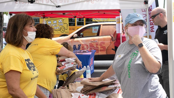 Volunteers collect and sort donated school supplies during Saturday's Stuff the Bus event.
