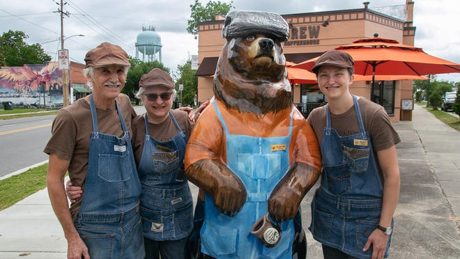 Proprietors Donovan and Roxanne Zook, and Regina Zook stand with the city's newest bear, 'Bearista Bear' at Crema Brew at Five Points. [Bill Hand / Sun Journal Staff