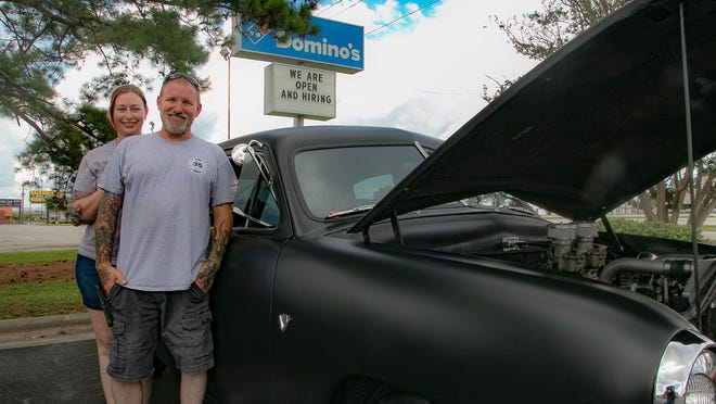 Greg and Kristy Stewart stand beside their antique Ford Tudor.