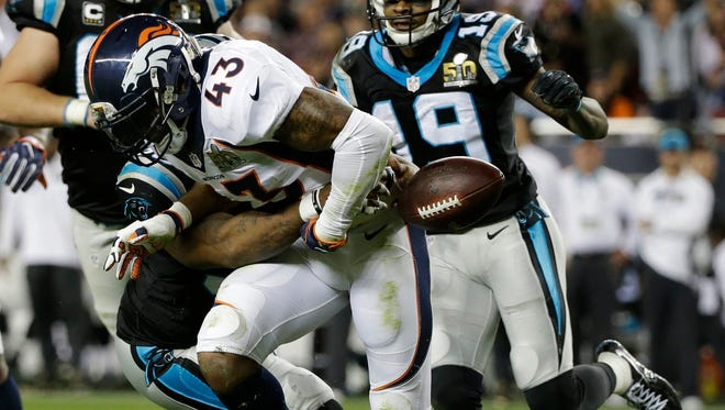 Carolina Panthers' Mike Tolbert, left, forces a fumble by Denver Broncos' T.J. Ward (43) during the second half.