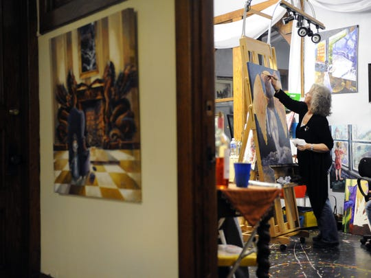 Linda Regula, of Tower Studios, works on a painting Jan. 2 at the Masonic Temple during the First Friday Art Walk in Zanesville. Eighteen studios and galleries and 14 businesses participated in the event.